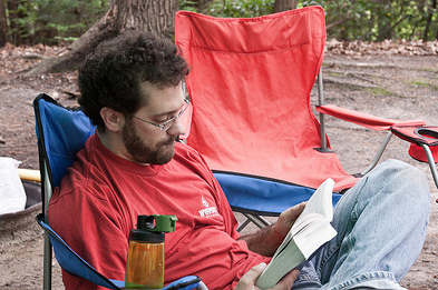 man reading a book while camping